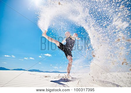 action shot of man kicking sand into the air in huge spray