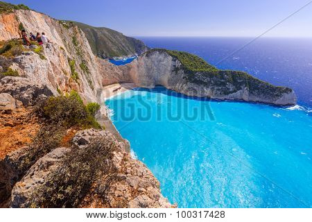 ZAKINTHOS, GREECE - AUG 22, 2015: Tourists on the cliff making photos of Navagio beach on Zakynthos, Greece. Navagio is called Shipwreck beach after smuggler ship Panagiotis was wrecked there in 1983.