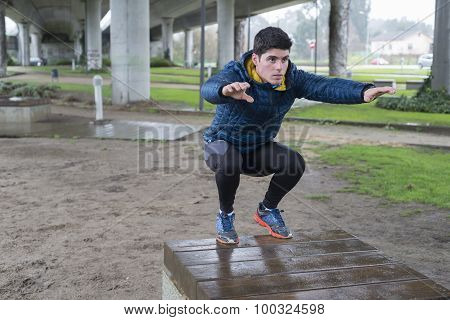 Man Squatting In A Park