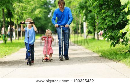 father with kids riding scooters in summer