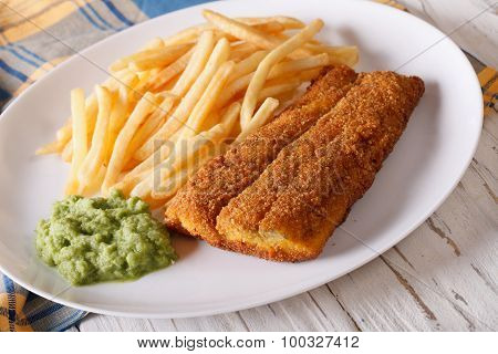 Fish In Breadcrumbs With Fried Potatoes Close-up. Horizontal