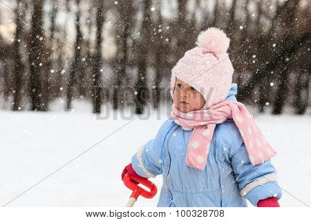cute toddler girl having fun in winter snow