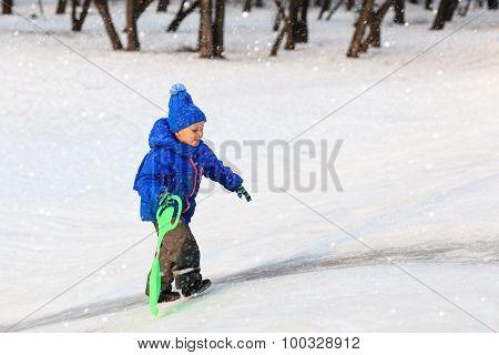 little boy play in winter snow