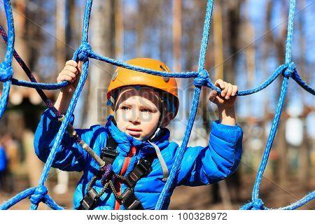 little boy climbing in adventure activity park