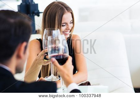 Man with happy elegant woman drinking red wine in restaurant