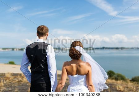Wedding Couple Looking Out To Sea