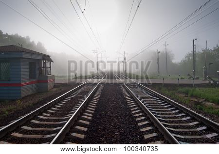 Beautiful railway with wires in fog at summer morning and railroad crossing