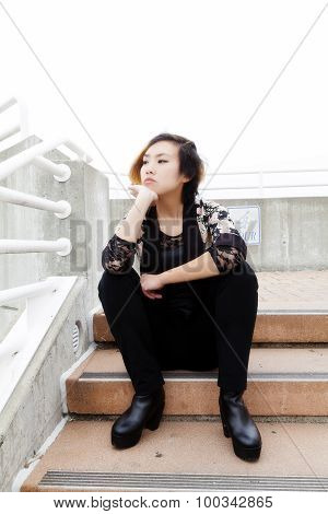 Skinny Asian American Woman Sitting On Outdoors Stairs