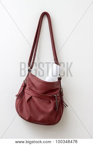 Red Bag Hanging  Over A White Wall