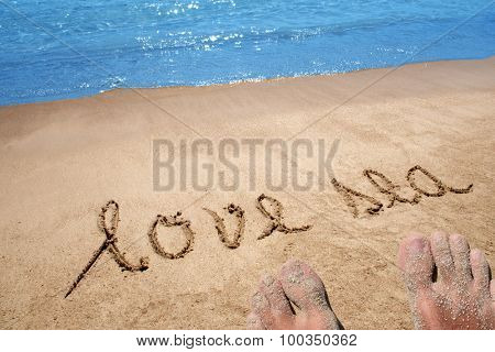 Conceptual handwritten love sea text in sand on a beach in an exotic island with feet