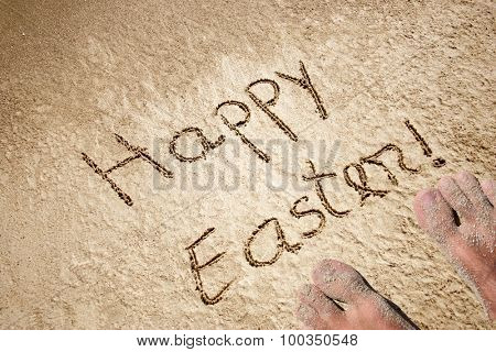 Concept or conceptual hand made or handwritten text in sand on a beach in an exotic island with feet