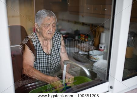 Elderly Woman Washing Dishes