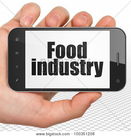 Manufacuring concept: Hand Holding Smartphone with Food Industry on display