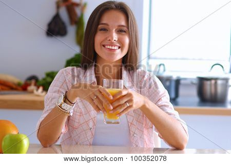 Young woman sitting a table  in the kitchen