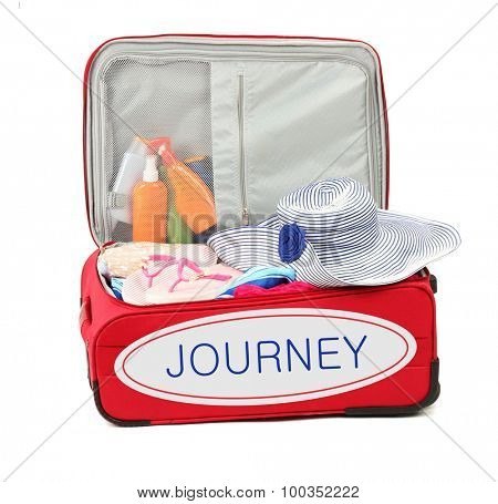 Journey concept. Suitcase with summer clothes, hat and suntan isolated on white