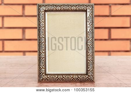 Old empty frame on table on brick wall background
