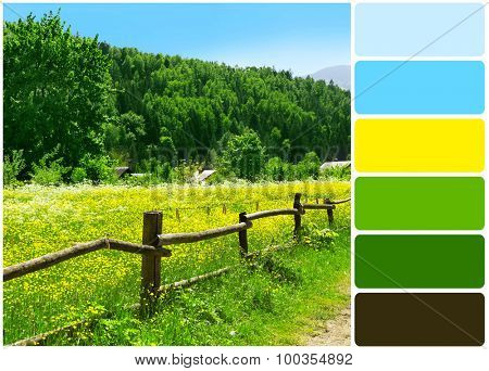 Wooden fence along beautiful meadow over mountain with grove of green trees and palette of colors