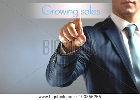 Businessman hand touching Growing sales icon