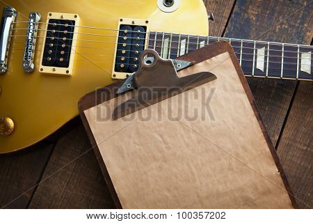 Vintage clipboard with gold electric guitar in background. Good for playlists, and production notes.