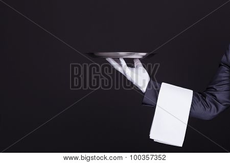 Image of a waiter hand holding an empty silver tray