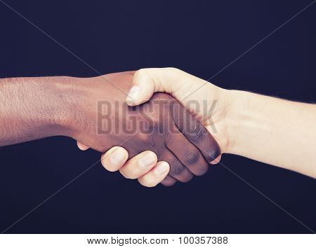 African and a caucasian man shaking hands over dark background