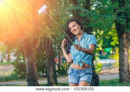 women hold monopod use smart phone take photograph selfie stick in park