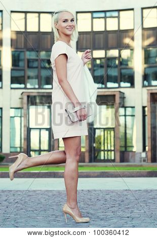 Beautiful blond young woman wearing dress and walking on the street