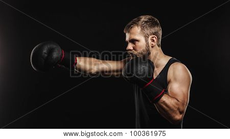 Athletic bearded boxer with gloves on a dark background
