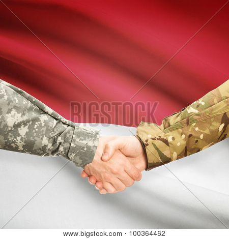 Men In Uniform Shaking Hands With Flag On Background - Monaco
