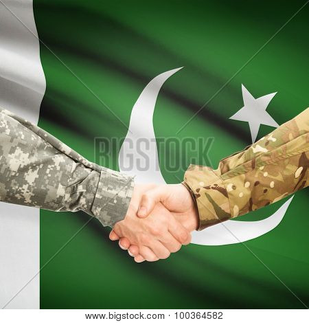 Men In Uniform Shaking Hands With Flag On Background - Pakistan