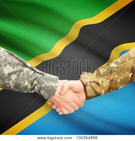 Men In Uniform Shaking Hands With Flag On Background - Tanzania