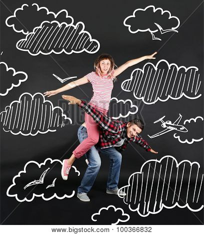 Funny young couple flying in the sky, on black background