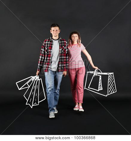 Funny young couple with shopping bags on black background