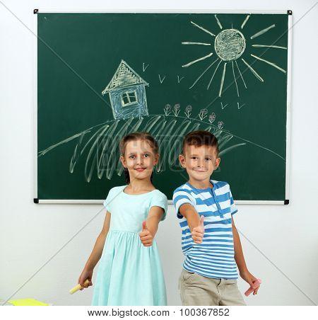 Children near blackboard at school