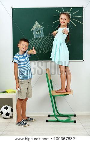 Children drawing on blackboard at school