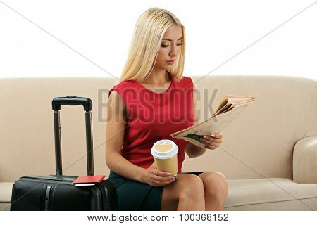 Woman with suitcase and tablet sitting on sofa and reading newspaper isolated on white