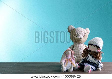 Dolls and teddy bear on blue background