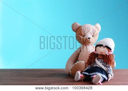 Doll and teddy bear on blue background
