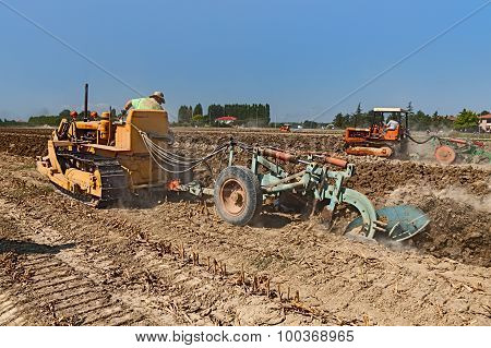 Farmer Plowing The Field With An Old Crawler Tractor Fiat