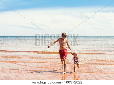 Little Girl And Boy Playing On The Beach