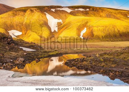 Light golden dawn illuminates the mountains and glaciers . The  sunrise in national park Landmannalaugar, Iceland