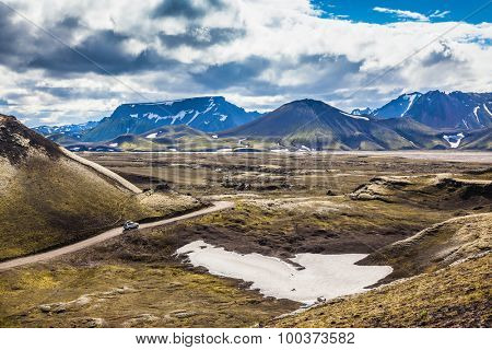 Summer trip to Iceland. The dirt road in a valley surrounded by mountains