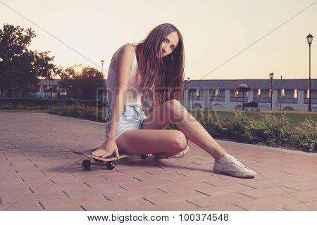 Instagram style image of cute girl sitting on her skateboard backlit