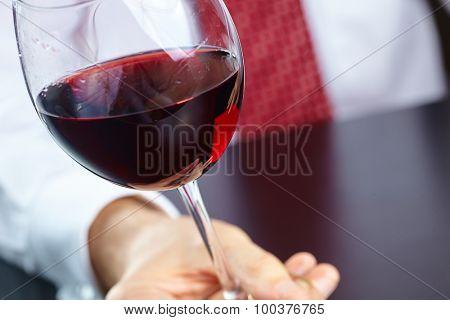 man handing glass of wine