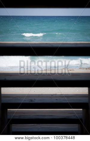 Ocean waves crashing on a sandy beach seen through the slates of wooden stairs.