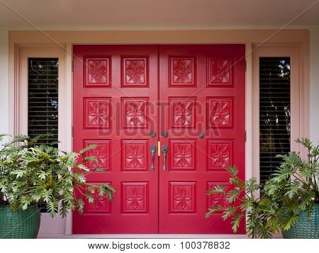 Red front doors with flower carvings at the entrance to an upscale home with Philodendron plants on each side.