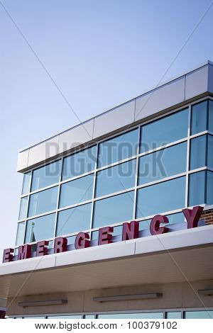 Emergency room entrance with red block letters on the metal awning of a hospital building, blue tone filter.