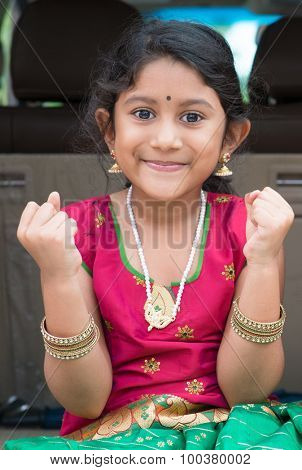 Excited Indian girl sitting in car smiling, ready to vacation. Asian child in traditional dress.