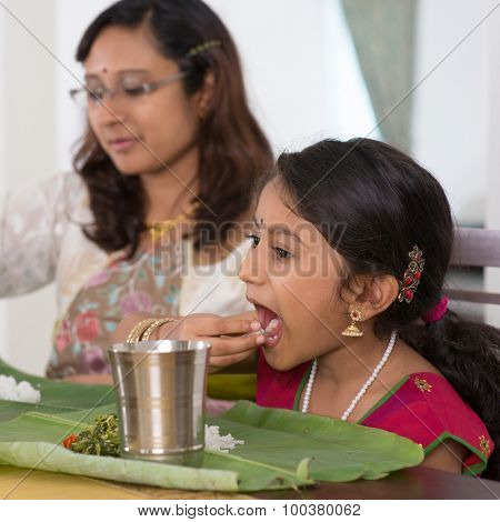 Indian family dining at home. Candid photo of India people eating rice with hands.