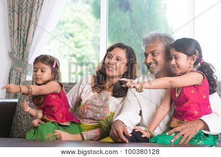 Happy Indian family at home. Asian people laughing and pointing to somewhere. Parents and children indoor lifestyle.